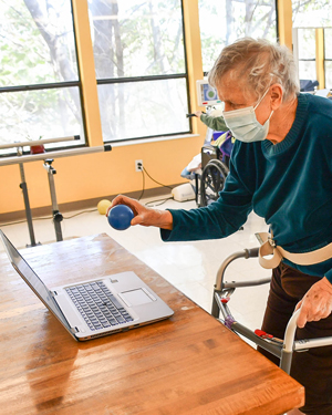 Standing and using RESTORE therapy program at Riverdale Center
